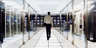 Man Walking In Server Room of Managed Services